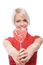Woman presenting a red heart shaped lollipop romantic affectionate to the viewer with happy smile as she celebrates valentines Royalty Free Stock Photography