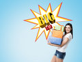 Woman with presents near a blue wall with big sale poster Royalty Free Stock Photo