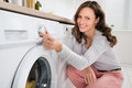 Woman pressing button of washing machine close up young in kitchen Royalty Free Stock Photos