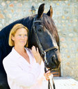 Woman with pretty black horse Stock Photos