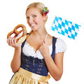 Woman with pretzel and bavarian flag happy young in a dirndl smiling a Stock Photo