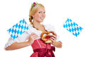 Woman with pretzel and bavarian flag smiling in a dirndl a a Royalty Free Stock Photos