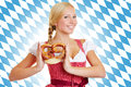 Woman with pretzel in a dirndl smiling attractive front of bavarian flag Royalty Free Stock Image
