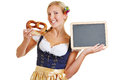 Woman with pretzel and empty blackboard happy bavarian in a dirndl Stock Photos
