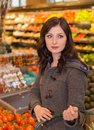 Woman in the produce section of a grocery store.