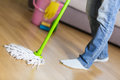 Woman in protective gloves using a wet-mop while cleaning floor Royalty Free Stock Photo