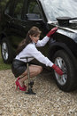 Woman pumping up car tyre