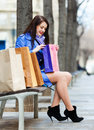Woman with purchases at bench in blue cloak Royalty Free Stock Image