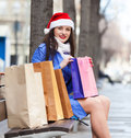 Woman with purchases at street smiling girl in city during the christmas sales Stock Photo