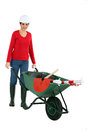 Woman pushing a wheelbarrow containing her tools Stock Photo