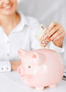 Woman puts euro cash into large piggy bank business office household school tax and education concept Royalty Free Stock Photography