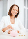 Woman putting coin into piggy bank business and money saving concept Royalty Free Stock Photography