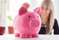 Woman putting coin in piggy bank financially smart saving money by coins Royalty Free Stock Photography