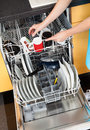 Woman putting dishes in the dishwasher happy utensils for cleaning Stock Photos