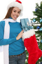 Woman putting gift in stocking Royalty Free Stock Image