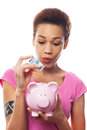 Woman putting money in piggy bank african american over white background Stock Images