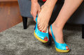 Woman putting on a pair of trendy blue shoes Royalty Free Stock Photo