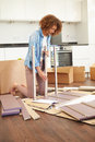 Woman putting together self assembly furniture in new home on her own Stock Photo
