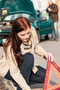 Woman putting triangle sign for car breakdown Royalty Free Stock Photography