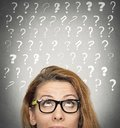 Woman with puzzled face expression and question marks above head Royalty Free Stock Photo