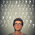 Woman with puzzled face expression and question marks above her head Royalty Free Stock Photo