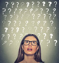 Woman with puzzled face expression question marks above her head looking up Royalty Free Stock Photo