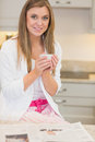 Woman in pyjamas with hot beverage reading newspaper Stock Photos