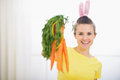 Woman in rabbit ears showing bunch of carrots Royalty Free Stock Photography