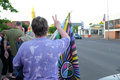 Woman with rainbow flag in crowd gives peace sign to passing motorists Royalty Free Stock Photo