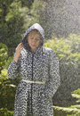 Woman and raincoat mature wearing rainy summer day green nature on background Royalty Free Stock Photos