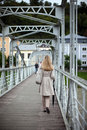 Woman in a raincoat walking away stylish beige across an urban pedestrian bridge Stock Photos