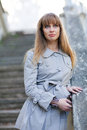 Woman in a raincoat young beautiful with blonde hair gray coat with blurred background Royalty Free Stock Photography