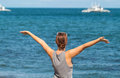 Woman with raised hands on the sea background. Happy girl in casual look on the seaside. Royalty Free Stock Photo
