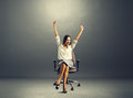 Woman raising hands up happy successful sitting on the chair and Royalty Free Stock Photography