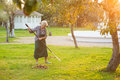 Woman with rake in garden. Royalty Free Stock Photo
