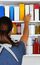 Woman reaching into pantry closeup of a her for a box of cereal the well stocked cabinet is full of canned food boxes and bottles Royalty Free Stock Photos