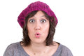 Woman reacting in amazement and wonder wearing a purple knitted beanie puckering her lips into an ooh expression with wide eyes on Stock Photos