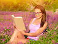 Woman read book outdoors attractive student girl sitting on pink floral field and doing homework wearing glasses education concept Royalty Free Stock Photography