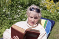 Woman reading aged an old interesting book sitting in a garden outdoor shot Royalty Free Stock Image