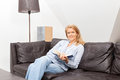 Woman reading a beautiful blond is sitting on a couch a book Stock Images