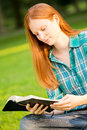 A woman reading a bible caucasian young christian outdoors in park Royalty Free Stock Photography