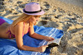 Young woman reading a book on the beach Royalty Free Stock Photo