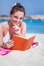 Woman is reading a book on a beach pretty brunette while lying Royalty Free Stock Photos