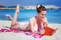 Woman is reading a book on a beach pretty brunette while lying Royalty Free Stock Photography