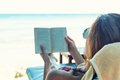 Woman reading a book at the beach sitting Stock Photos