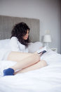 Woman reading book in bed Stock Images