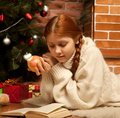 Woman reading book on Christmas in front of tree Royalty Free Stock Photos