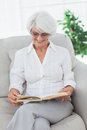 Woman reading a book on a couch mature Royalty Free Stock Photography