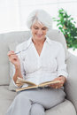 Woman reading a book on the couch mature Stock Image