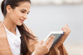 Woman reading book covered with blanket young beautiful sitting on beach Royalty Free Stock Photography